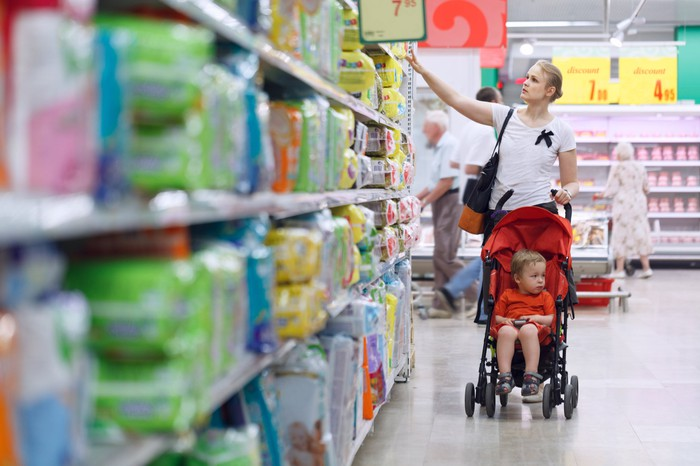 A shopper looking at baby care products in a supermarket and pushing a stroller.