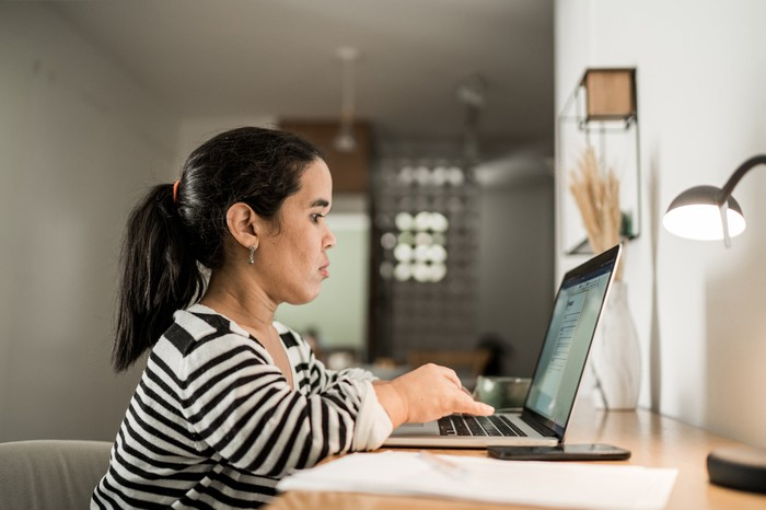 A person sitting at a desk typing on laptop.