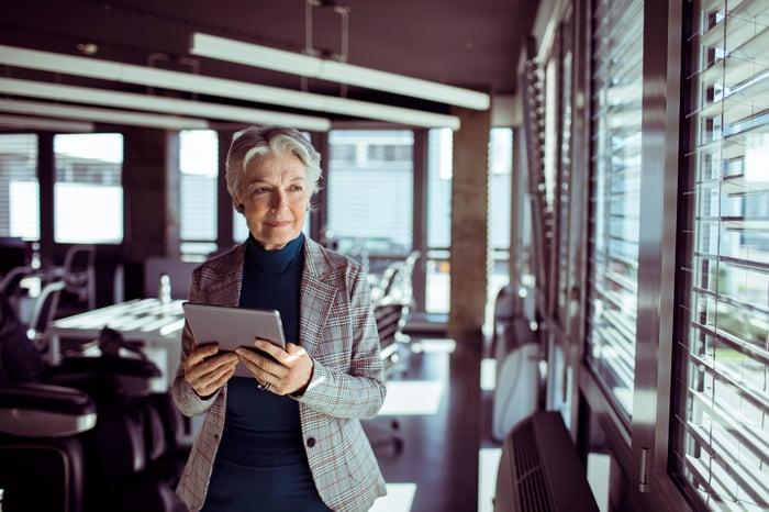 Une personne debout dans un café, tenant une tablette, regardant par la fenêtre avec un sourire complice.