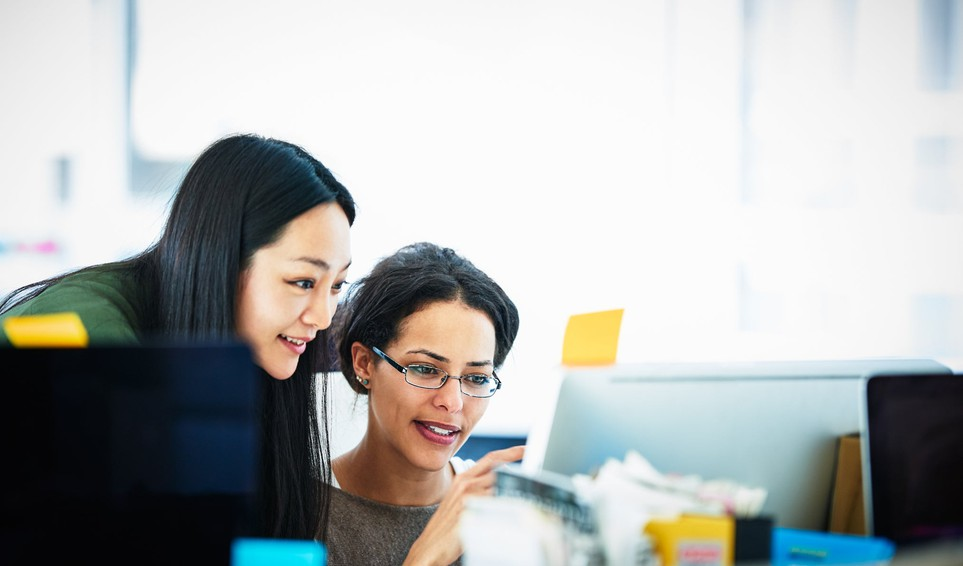 two_women_discussing_in_front_of_laptop