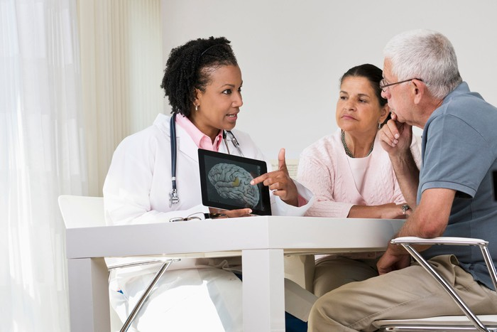A doctor shows a brain scan to an older couple looking on intently.