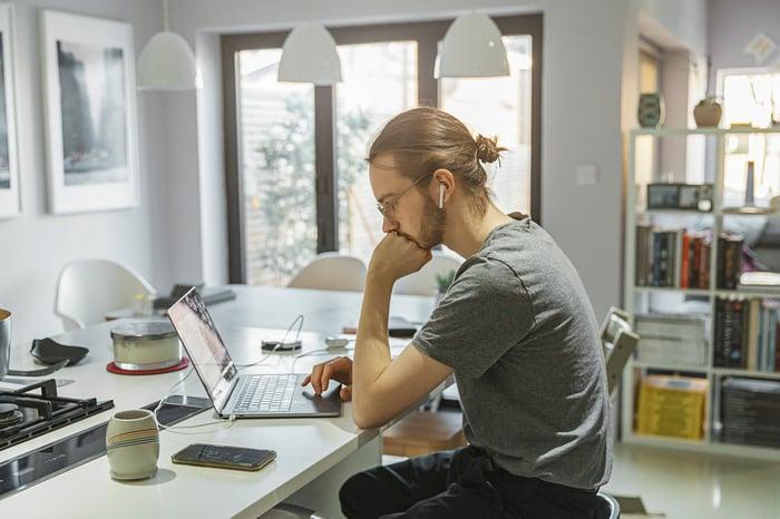 Man sitting in kitchen on laptop