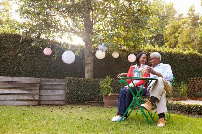 Un couple d'âge mûr buvant du vin à une table sur une pelouse.