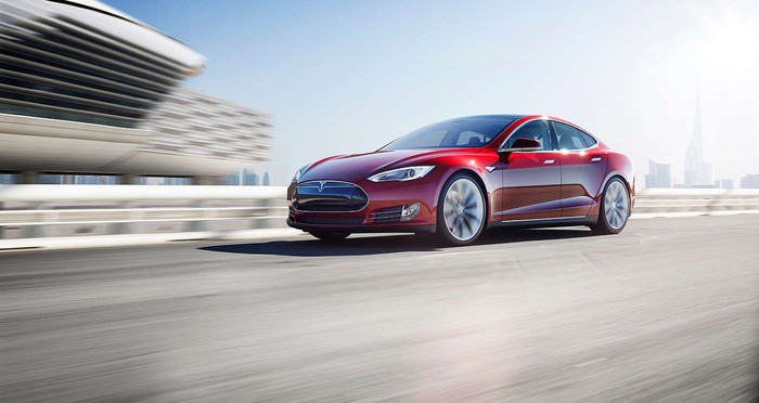 Tesla Model S on a highway with an urban skyline in the background.