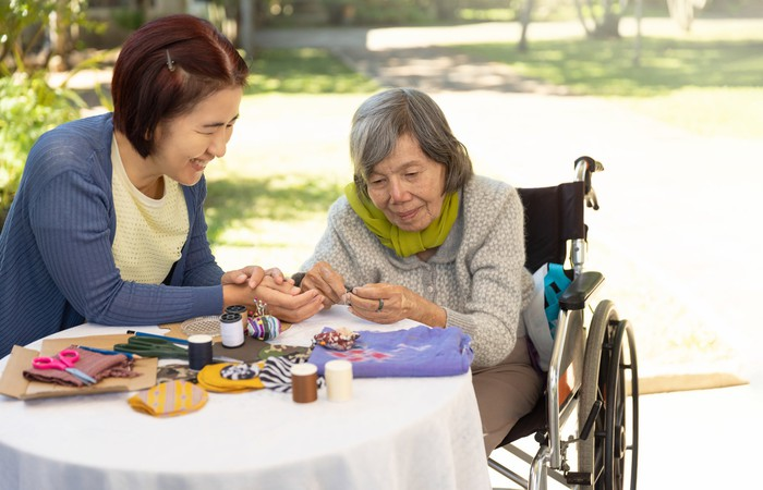 A person helping an older person in a wheel chair put together a puzzle at a table outdoors.