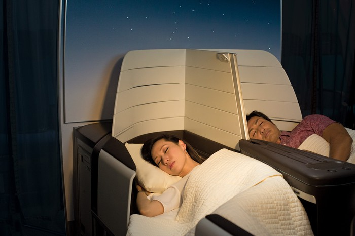 Two people sleeping in flat-bed seats on an airplane.