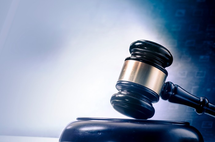A judge's gavel resting on a wooden stand, with hazy digital numbers superimposed.