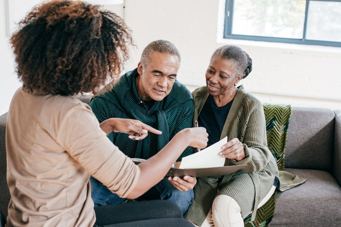 A person explaining insurance forms to an older couple seated on a sofa.