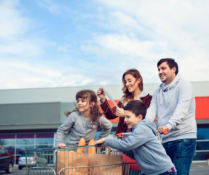 A family in a parking lot with a shopping cart full of groceries.