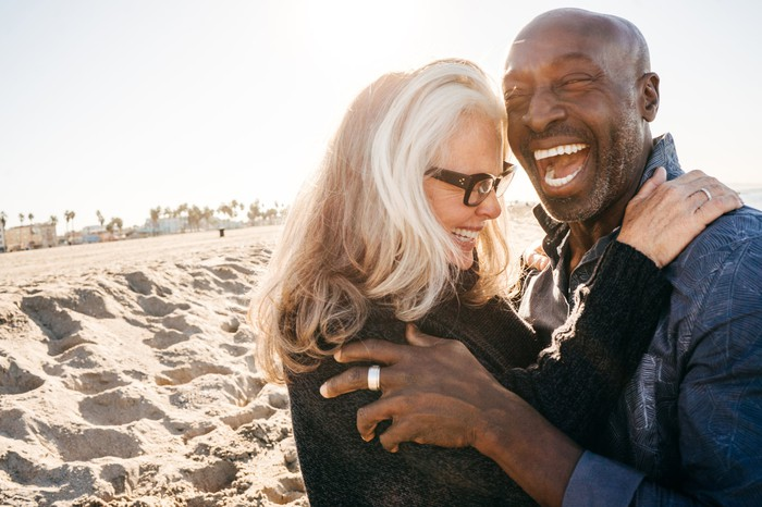 Retired couple hugging and laughing on the beach.