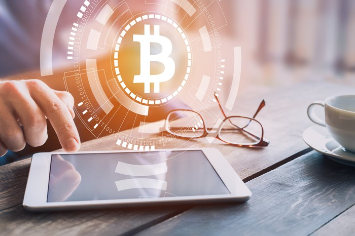 A bitcoin symbol emanating from a tablet on a table.