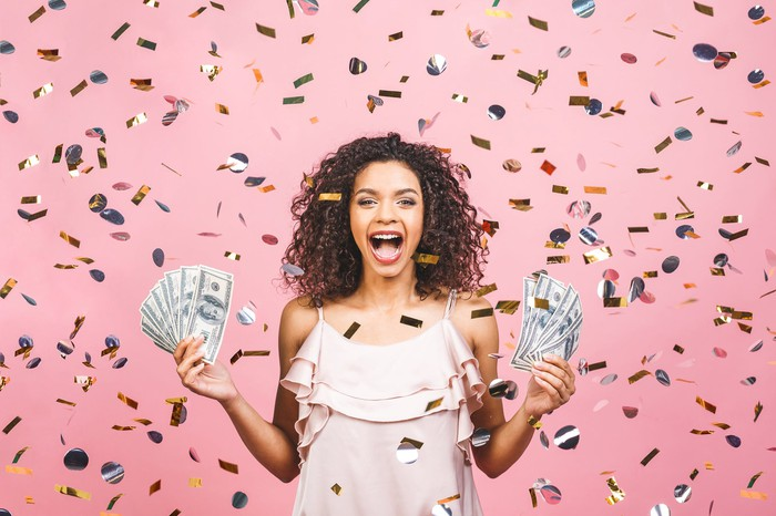 A smiling person holds cash while being showered with confetti.
