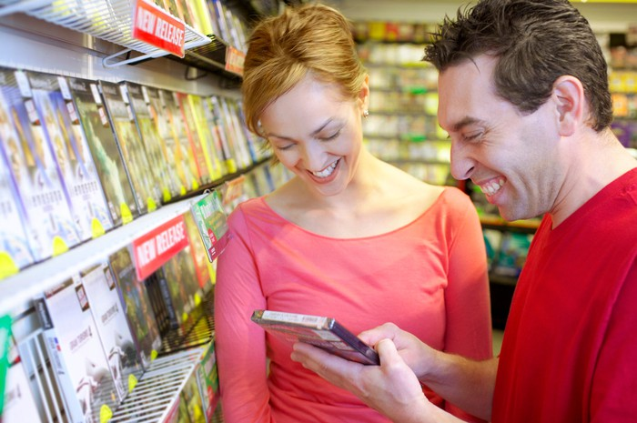 Two people getting excited about a software title at a video game store.