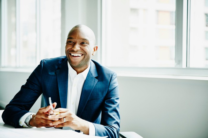 A businessman smiling at his desk, holding his phone but looking off at something else.