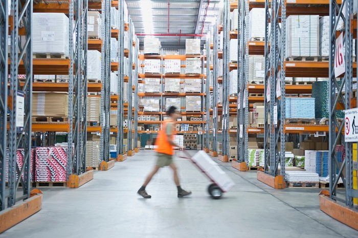 A warehouse worker pushes a dolly down a long aisle.