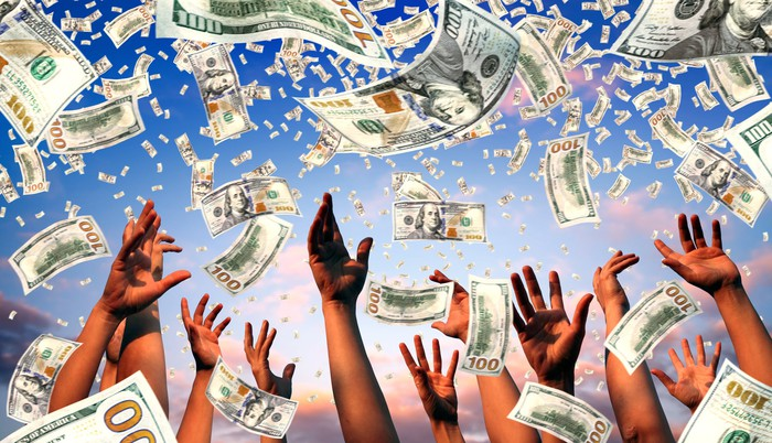 Hands reaching up as $100 bills fall from sky.