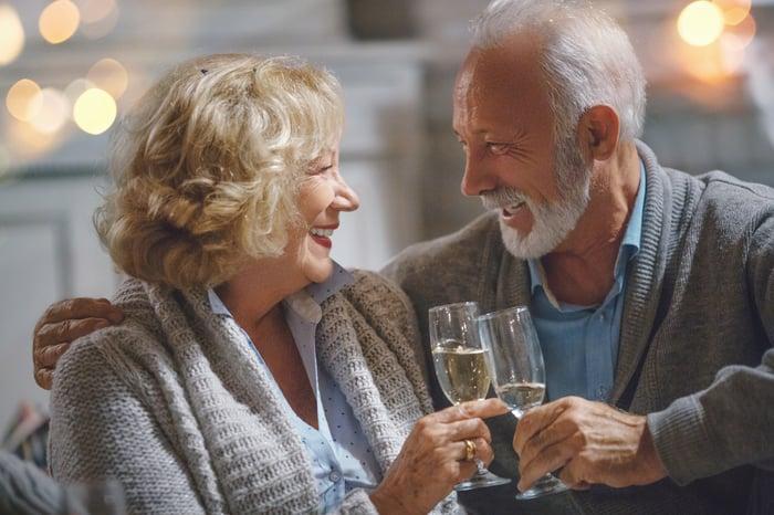 Smiling seniors clinking champagne glasses.
