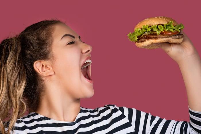 Woman ready to take big bite of a burger