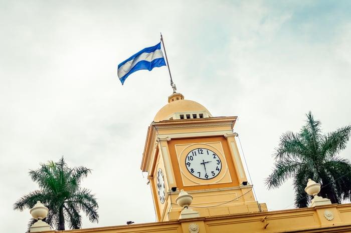 The flag of El Salvador flies above the clock tower of a building in the city of Santa Ana, El Salvador.