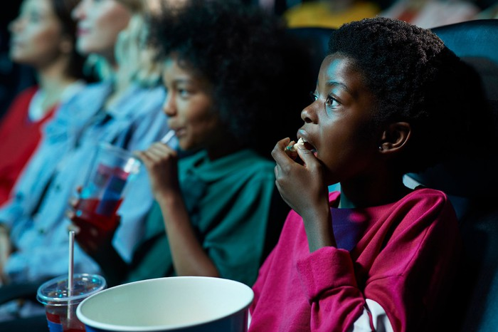 Kids eating popcorn inside a movie theater while watching a movie.