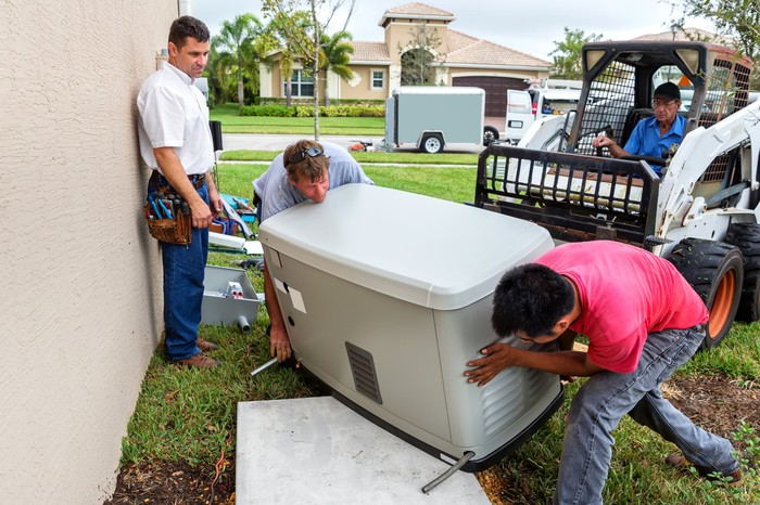 Several workers moving a generator into position near a home.