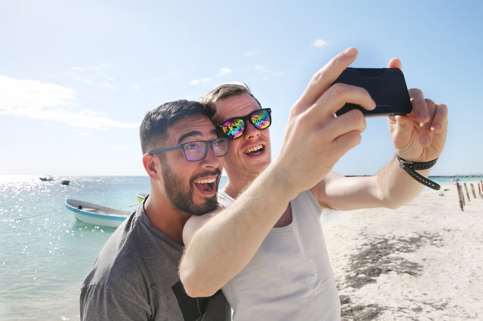 Two people taking a selfie at the beach.
