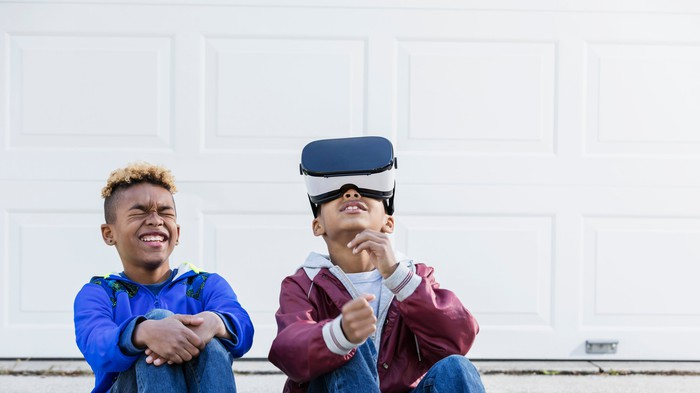 Two kids sitting together, with one wearing a virtual reality headset.