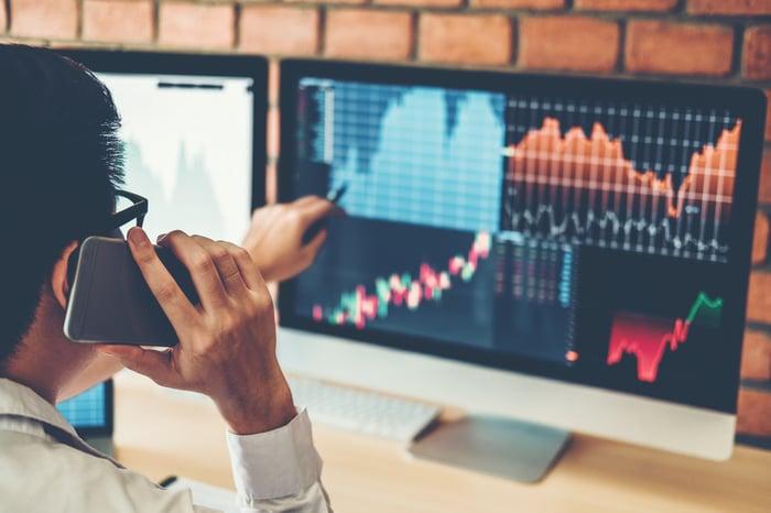 Trader évaluant la hausse du prix des actions sur l'écran de l'ordinateur.