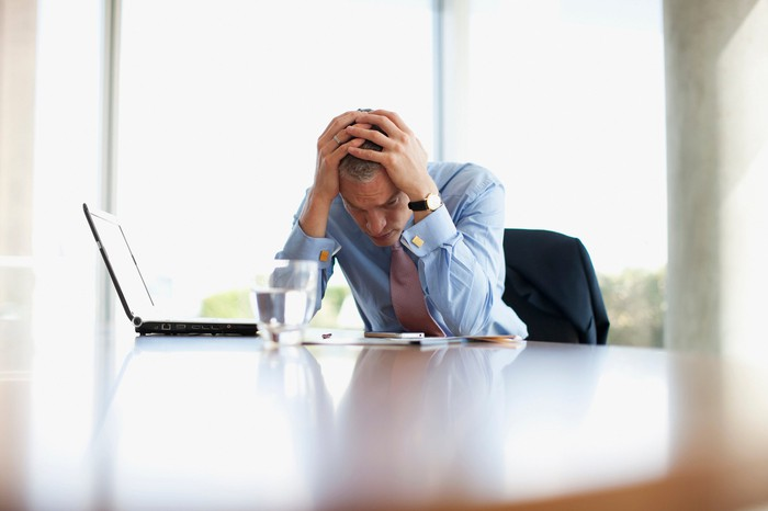 Stressed-out businessperson sitting at desk, with laptop.
