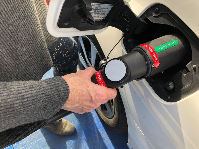 A person fueling a hydrogen-powered vehicle.