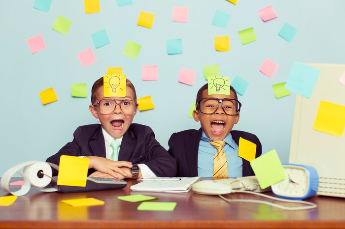 Two children dressed as businessmen play with sticky notes.