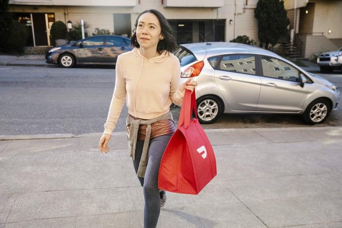 Woman carrying DoorDash bag