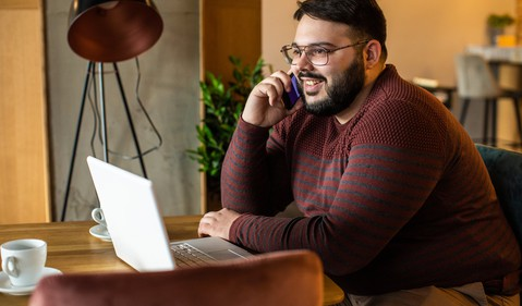 GettyImages-man smiles on phone at computer