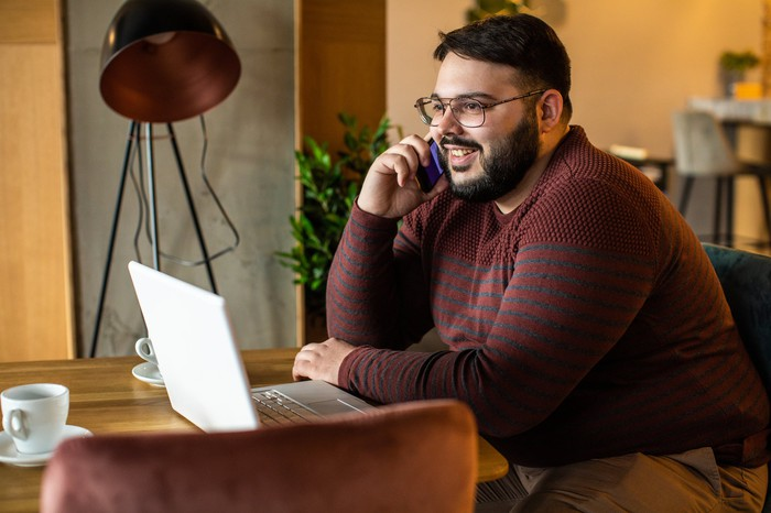 An investor smiles while speaking on the phone and looking at his laptop.