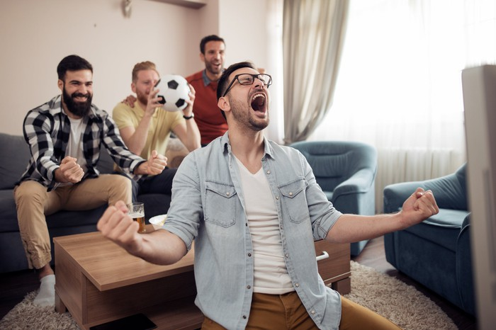 Four men in a living room cheer at the television. One is holding a soccer ball.