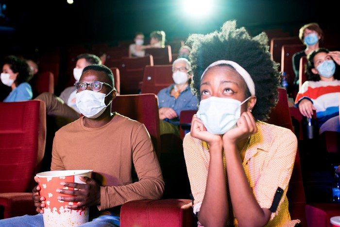 Masked patrons enjoying a movie at a theater.