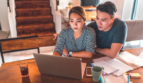 Serious couple looking at laptop and discussing finances