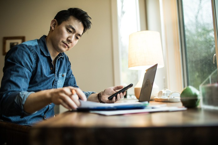 An investor works at a laptop in his home office while holding a mobile phone.