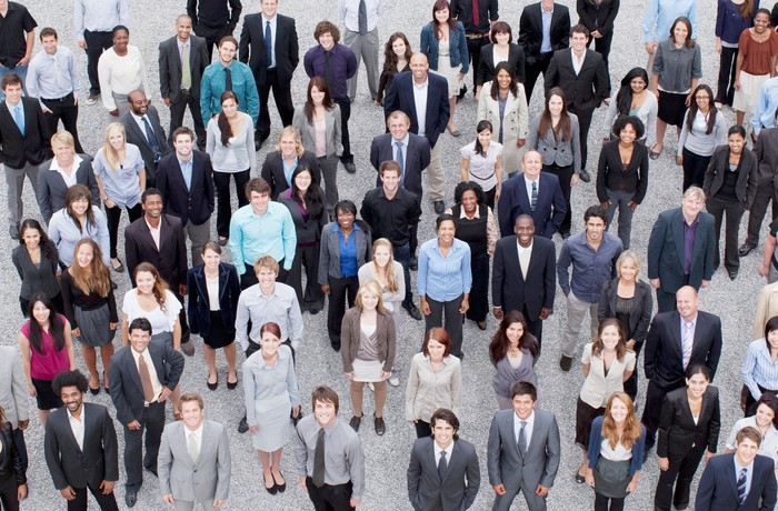 A large diverse crowd of people in business attire looking toward the sky.