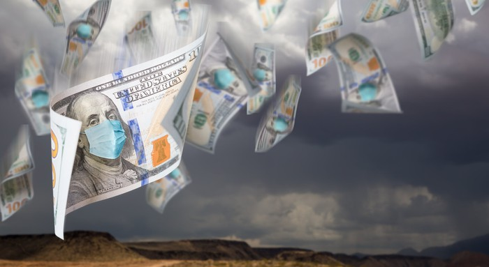 $100 bills with face masks on Benjamin Franklin falling from a stormy, cloudy sky.