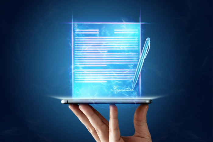 Fingers balancing a mobile device with an e-signature icon projected above the device.
