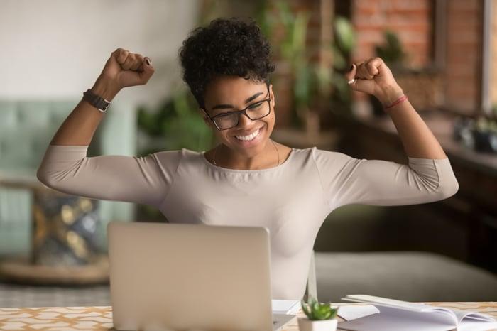 Une personne levant les bras en signe de triomphe devant un ordinateur.