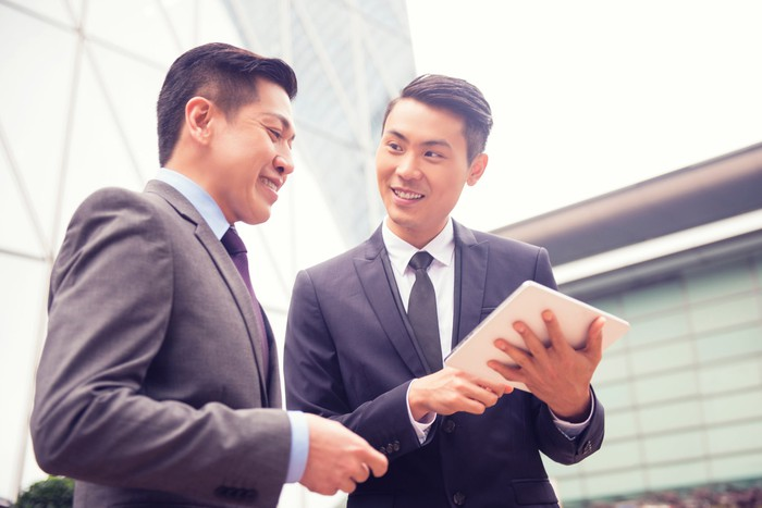 Two young men in business suits converse looking at a tablet.
