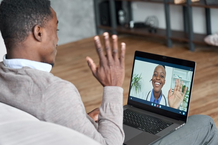A patient sitting on the sofa using a laptop computer to conduct a virtual doctor's visit.