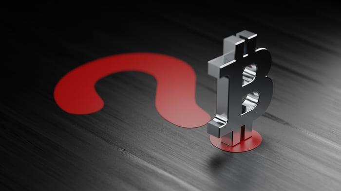 Un symbole Bitcoin argenté se dresse sur un grand point d'interrogation rouge.