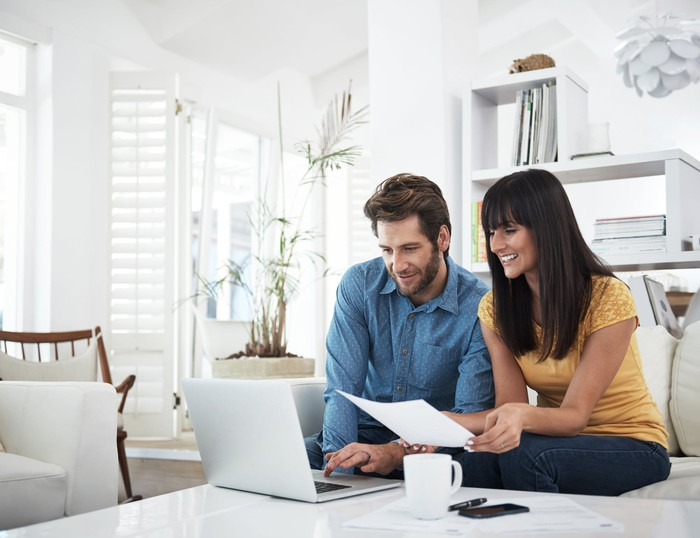A smiling man and woman sitting together on a couch and looking at a computer and a sheet of paper.