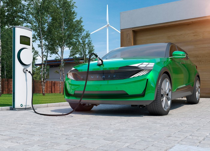 A green electric vehicle is being charged.