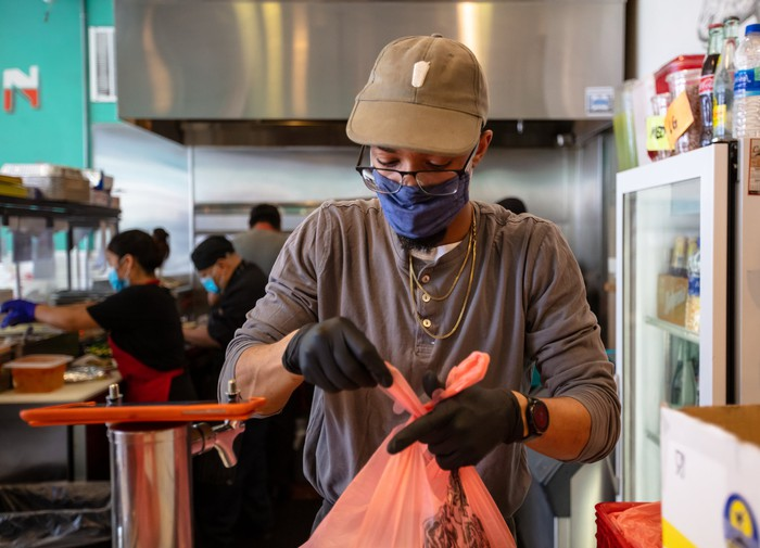 Fast-food worker bagging up an order.
