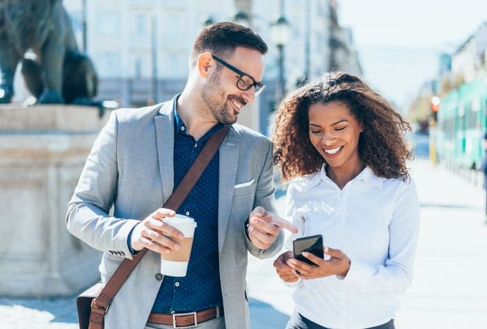 Two people laughing at something on a smartphone while walking down the street.