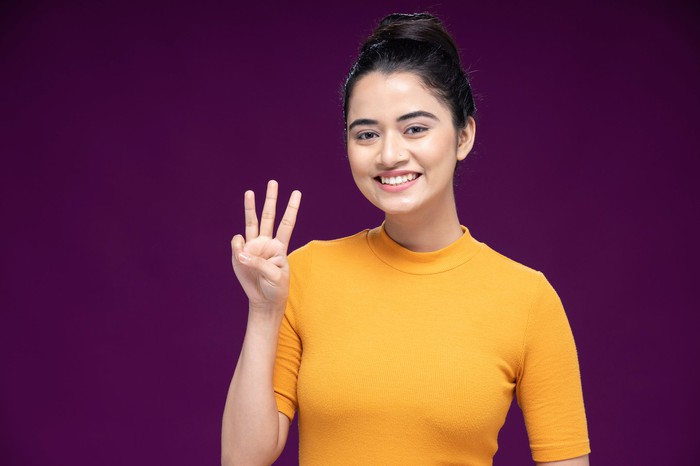 A woman is holding up three fingers.